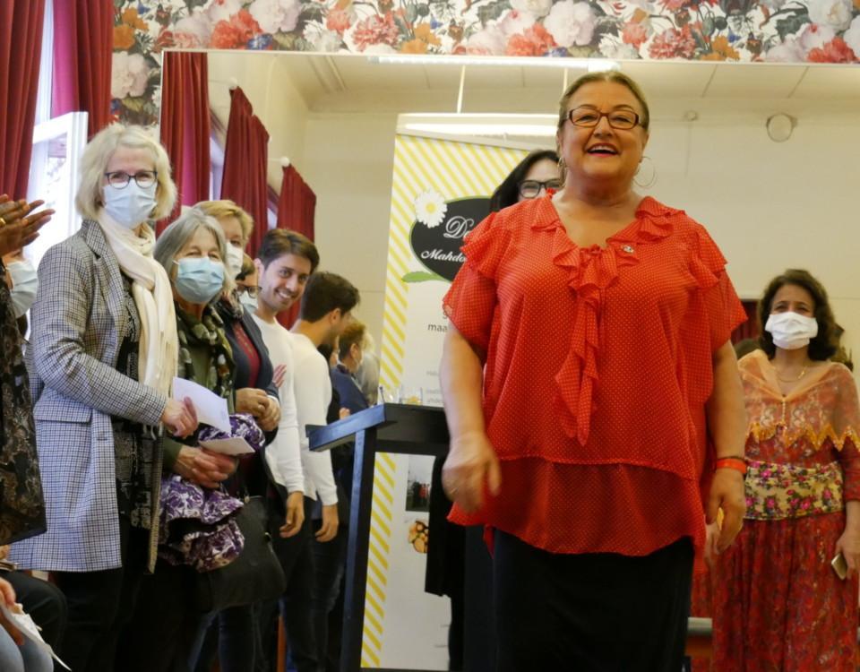 kvinna ler och går mot kameran, omringad av människor