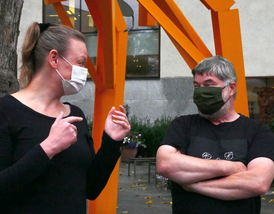 två munskyddsbeklädda personer tittar på varandra