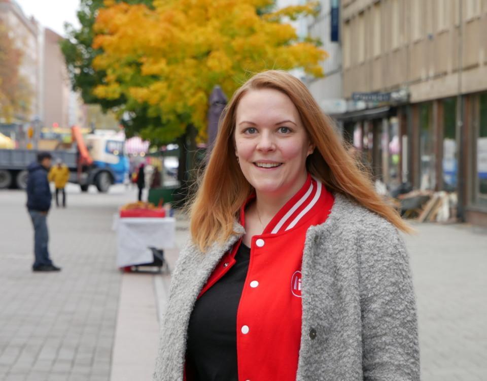 En kvinna står på en gågata och ler mot kameran, höstlöv i bakgrunden