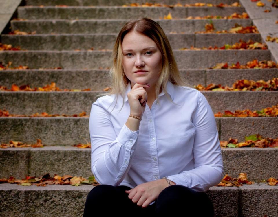 Ung kvinna sitter på en trappa.