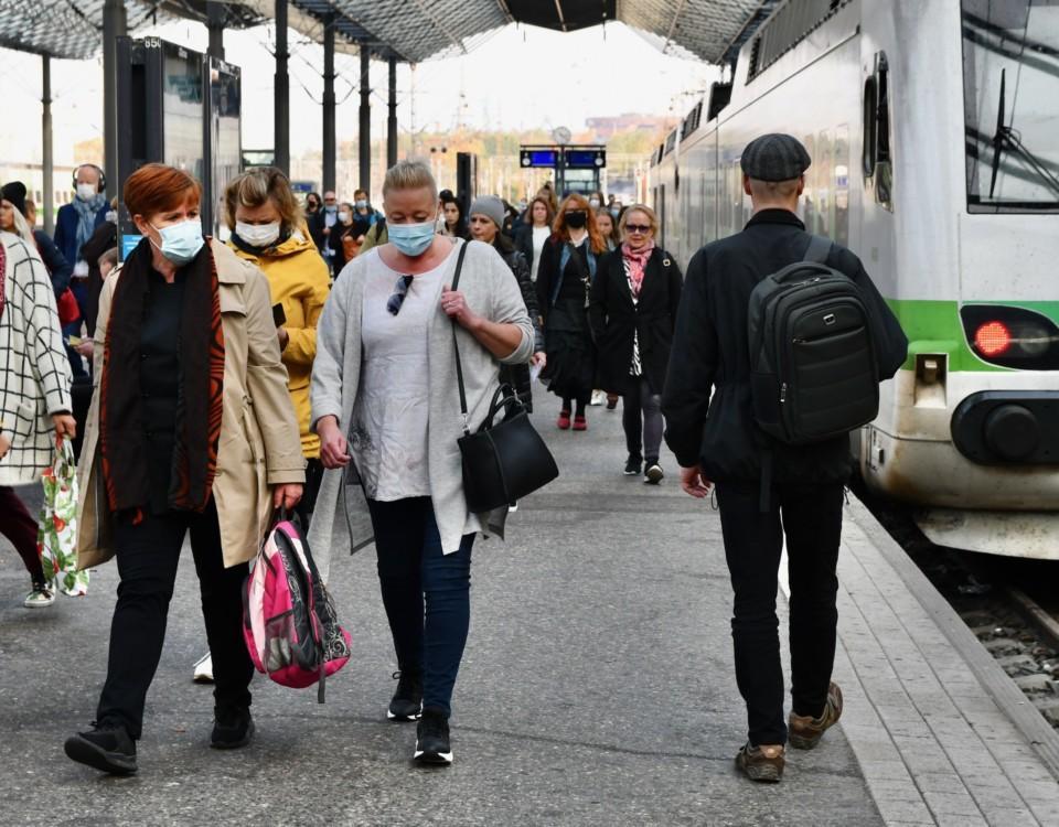 Människor med munskydd på en perrong.