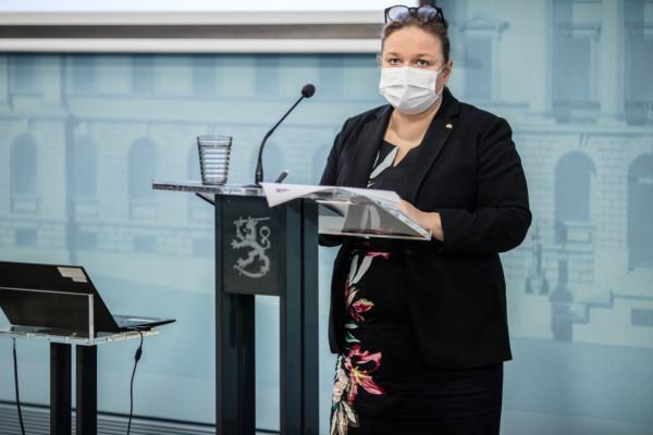 Kvinna i munskydd vid en talarstol.
