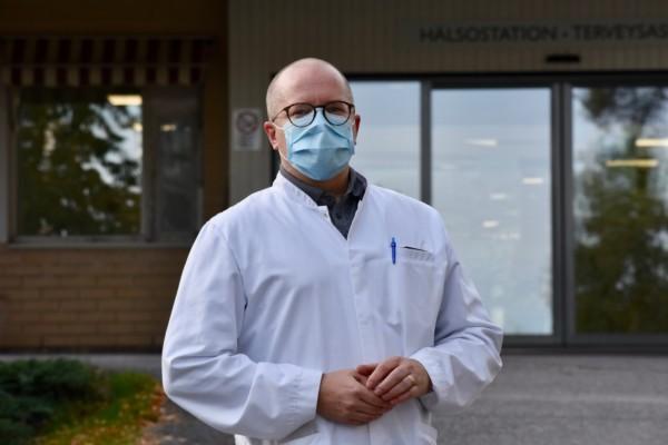 Man i mask framför hälsostation.