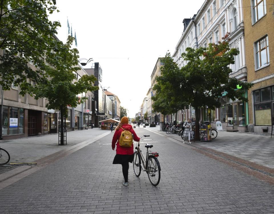 människa leder cykel på rätt tom o öde gata