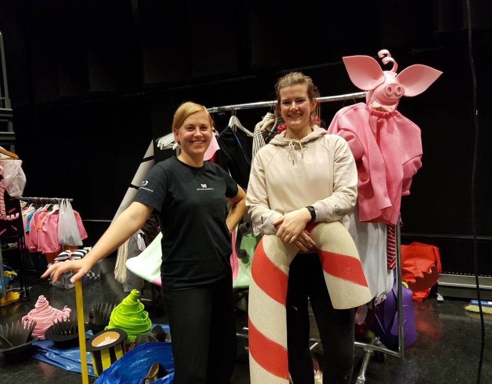 två kvinnor på teaterscen med godisrekvisita