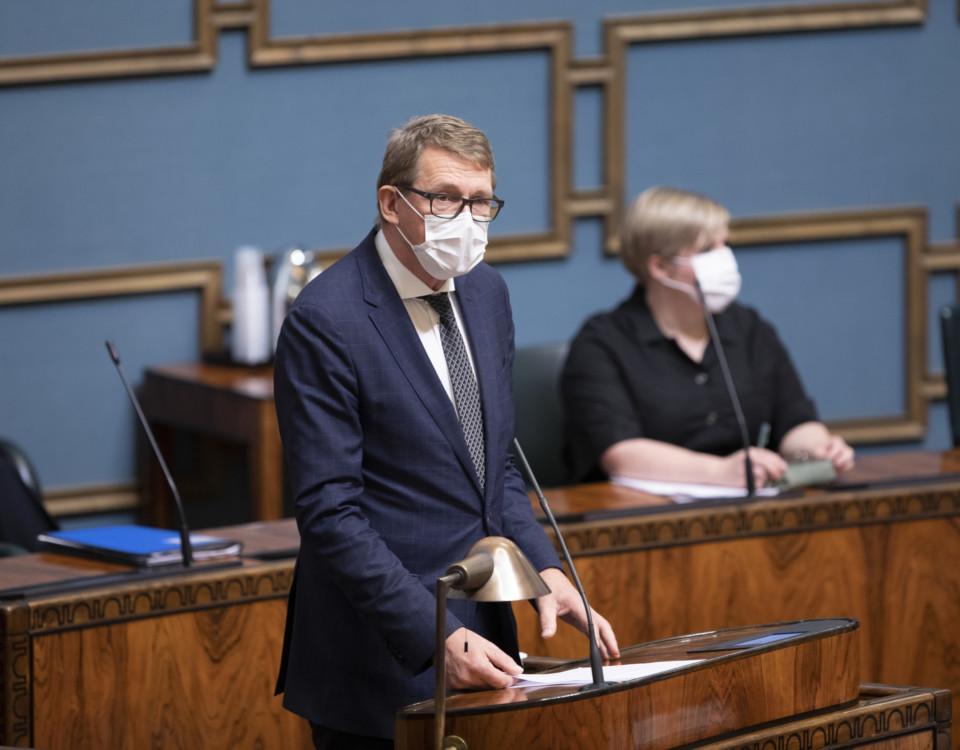 Kostymklädd herre i ansiktsmask vid riksdagens plenisals podium
