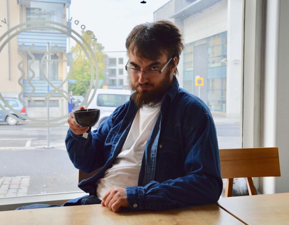 Un man dricker kaffe el te ur mugg