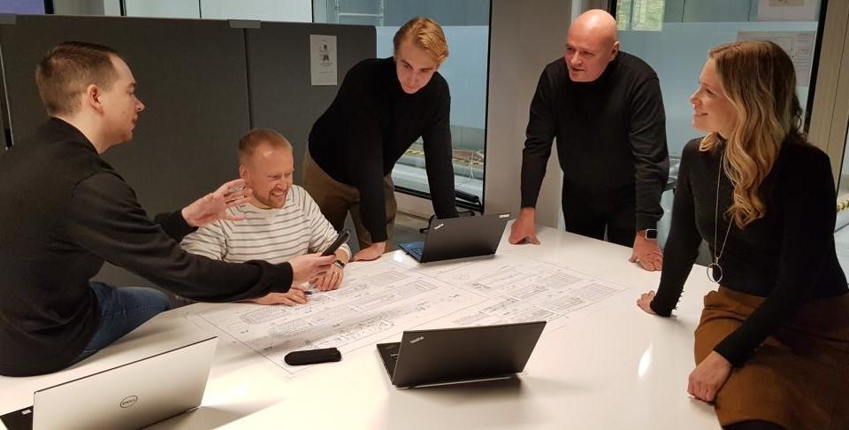 Fem personer kring ett planeringsbord.