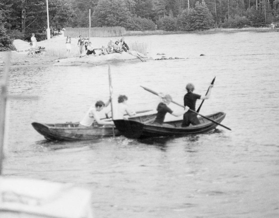 Svartvitt fotografi på barn i roddbåtar.