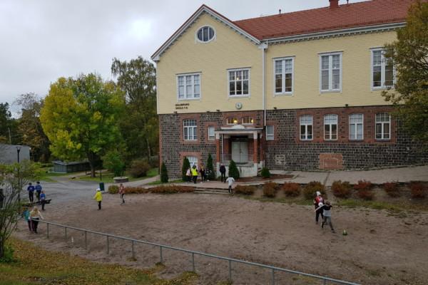 skolhus. Elever syns på gården.