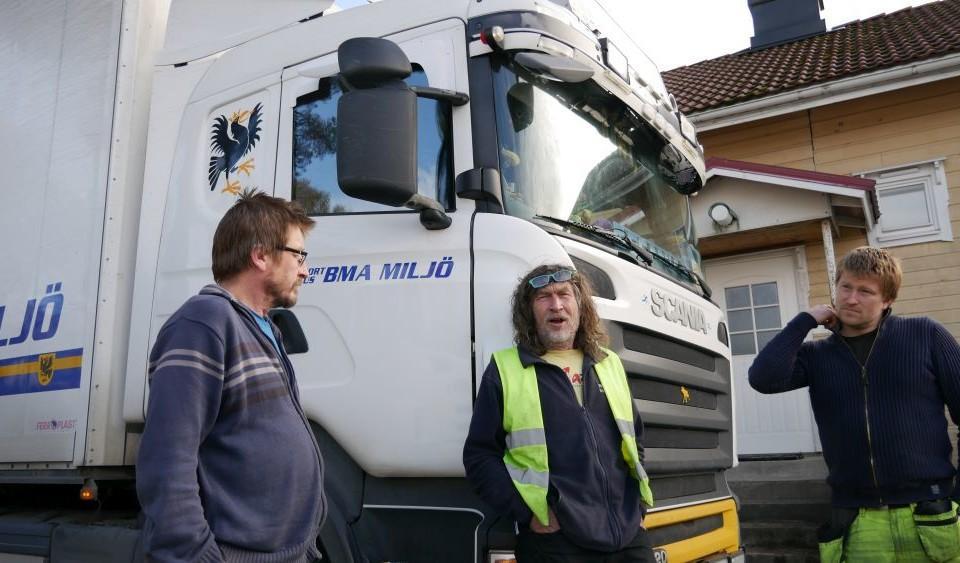 tre män iklädda arbetskläder står framför en lastbil