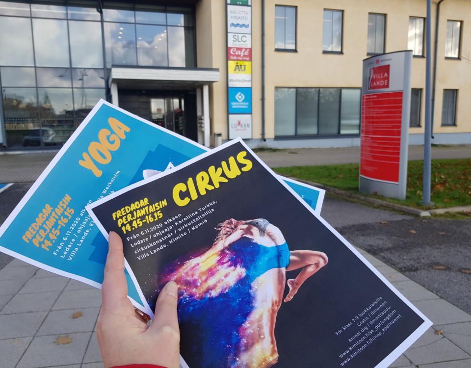Två flyers- cirkus och yoga - i en hand framför ett kulturhus