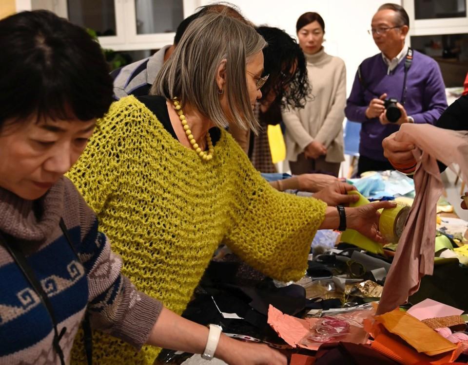 Många människor som rotar runt bland färger och textilprover på ett bord.