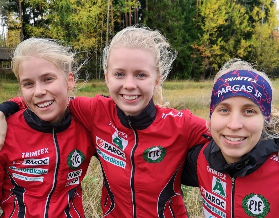 Tre unga kvinnor i orienteringskläder.