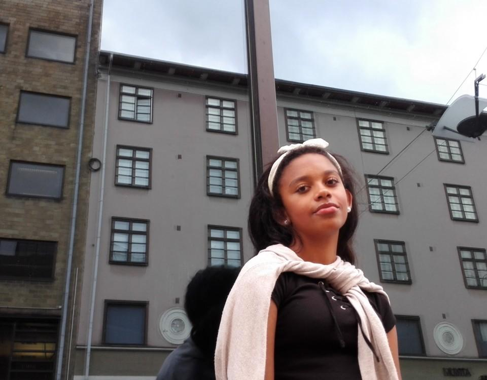 Ung kvinna står och lutar mot en spegelvägg