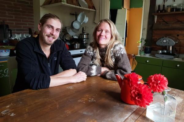Två personer vid ett träköksbord i gammaldags kök