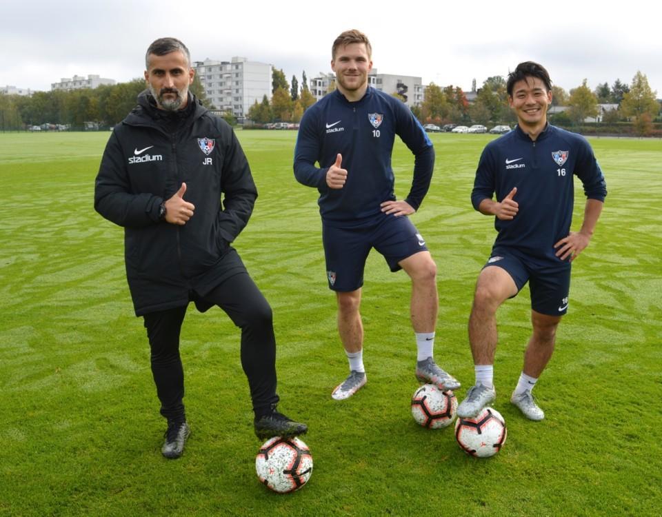Tre män på en fotbollsplan med en boll.
