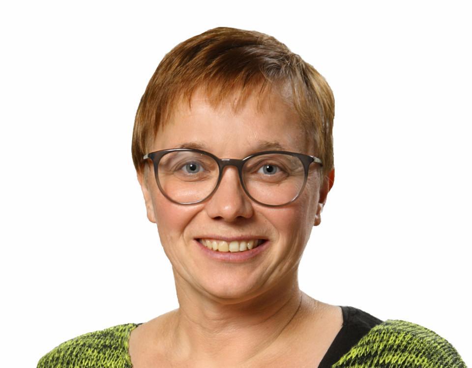 En kvinna med kort hår och glasögon ler mot kameran.