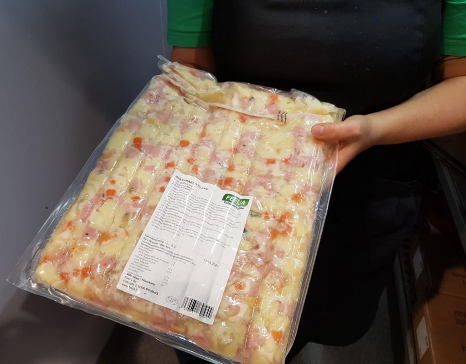 En rektangulär plastförpackning genom vilken potatis- och korvbitar syns i spad.