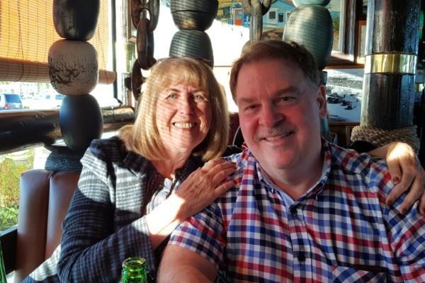 man och kvinna sitter vid ett bord och ler mot kameran