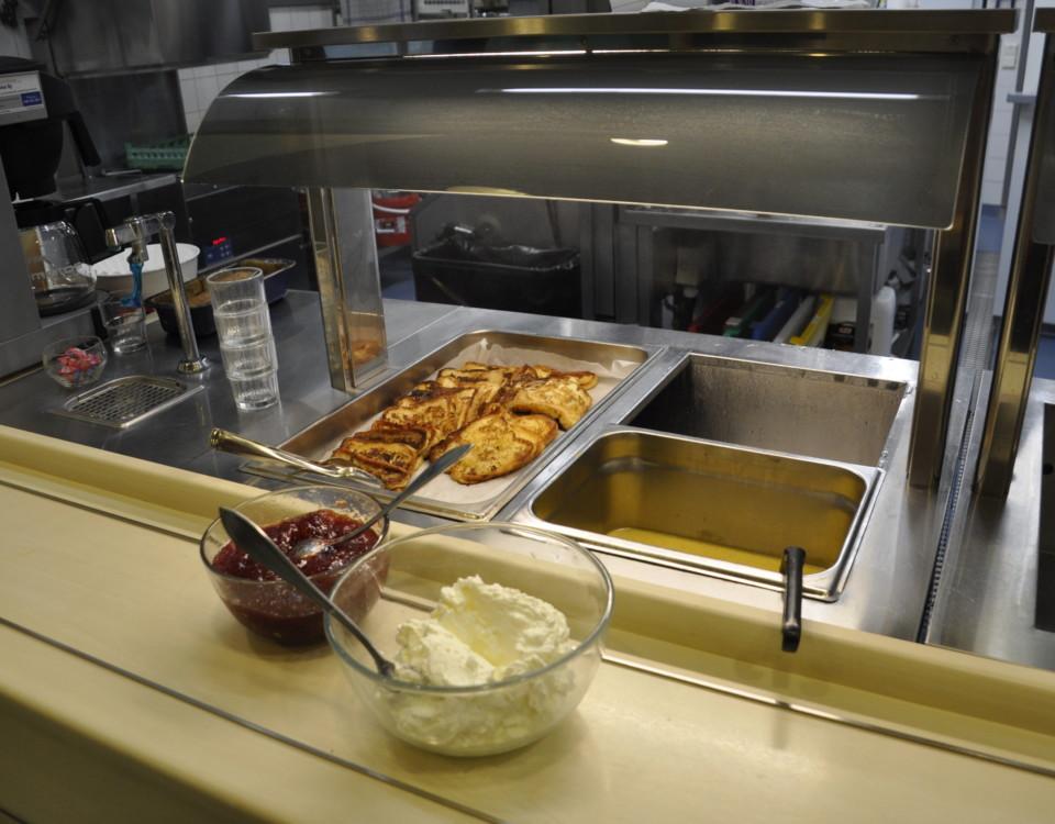 Aluminiumformar med dagens lunch: purésoppa, fattiga riddare, sylt och grädde syns