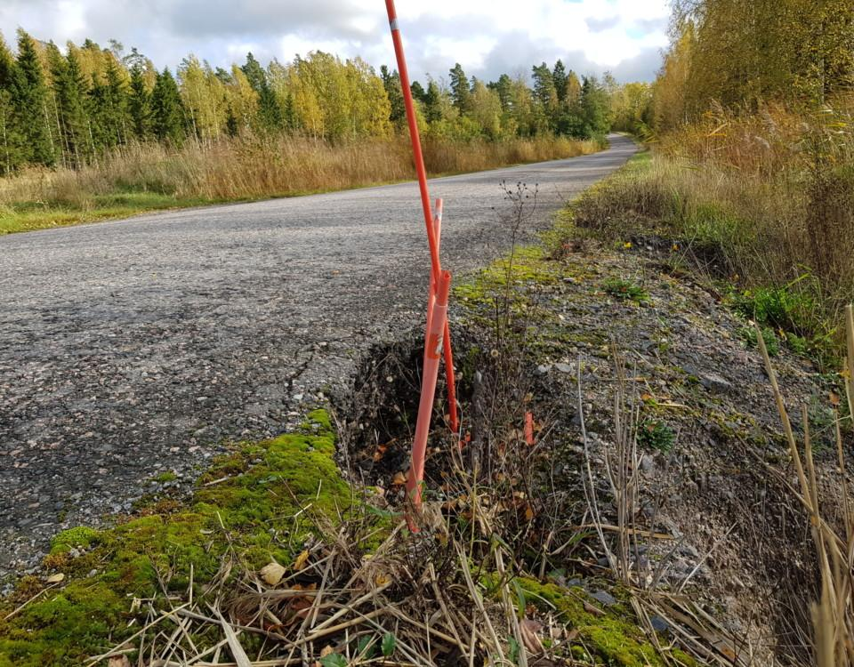 ett hål vid kanten av en asfalterad väg