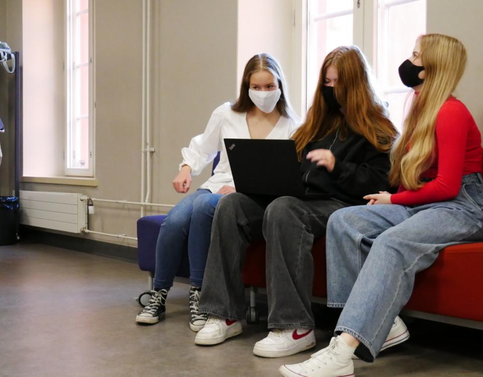 tre gymnasieelever med munskydd sitter samlade kring en laptop på en soffa