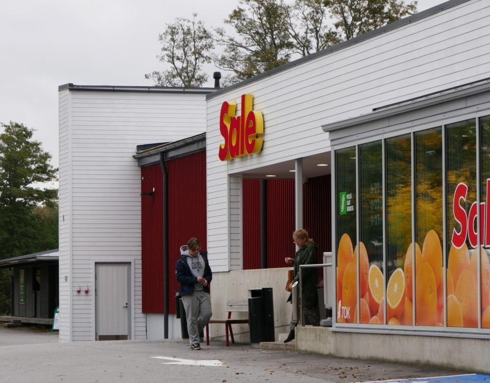 två personer möts vid ingången till en matbutik