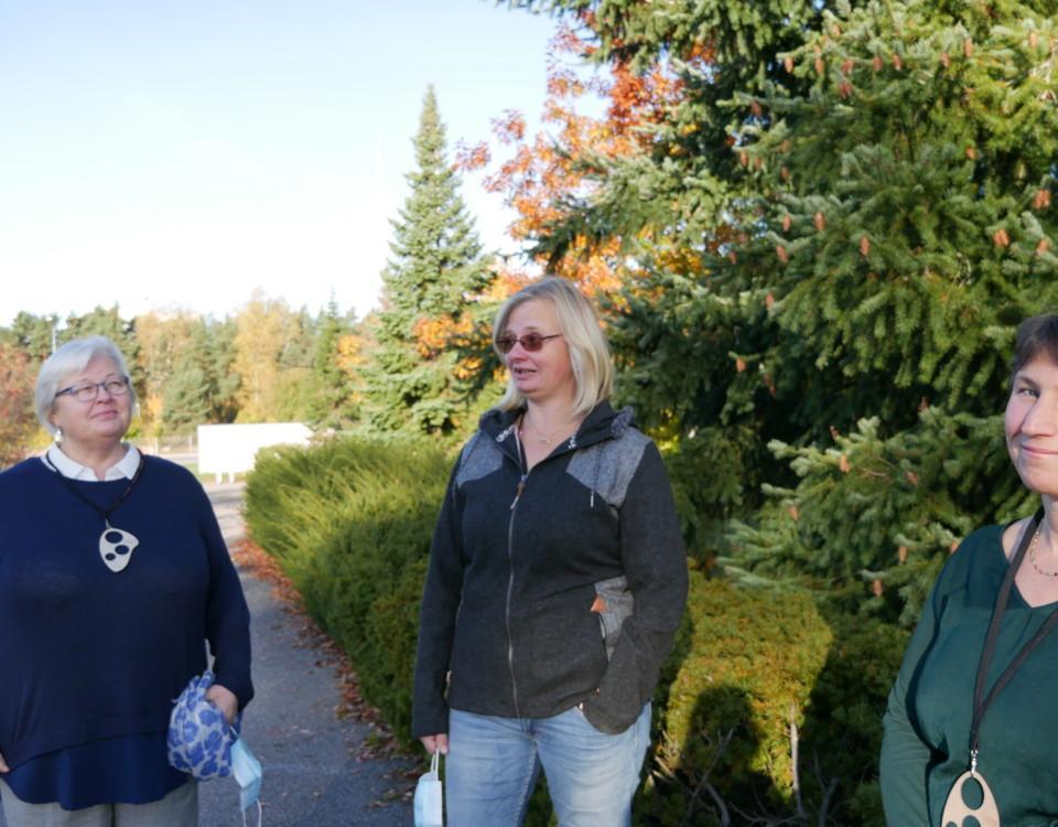 tre kvinnor står och pratar utomhus