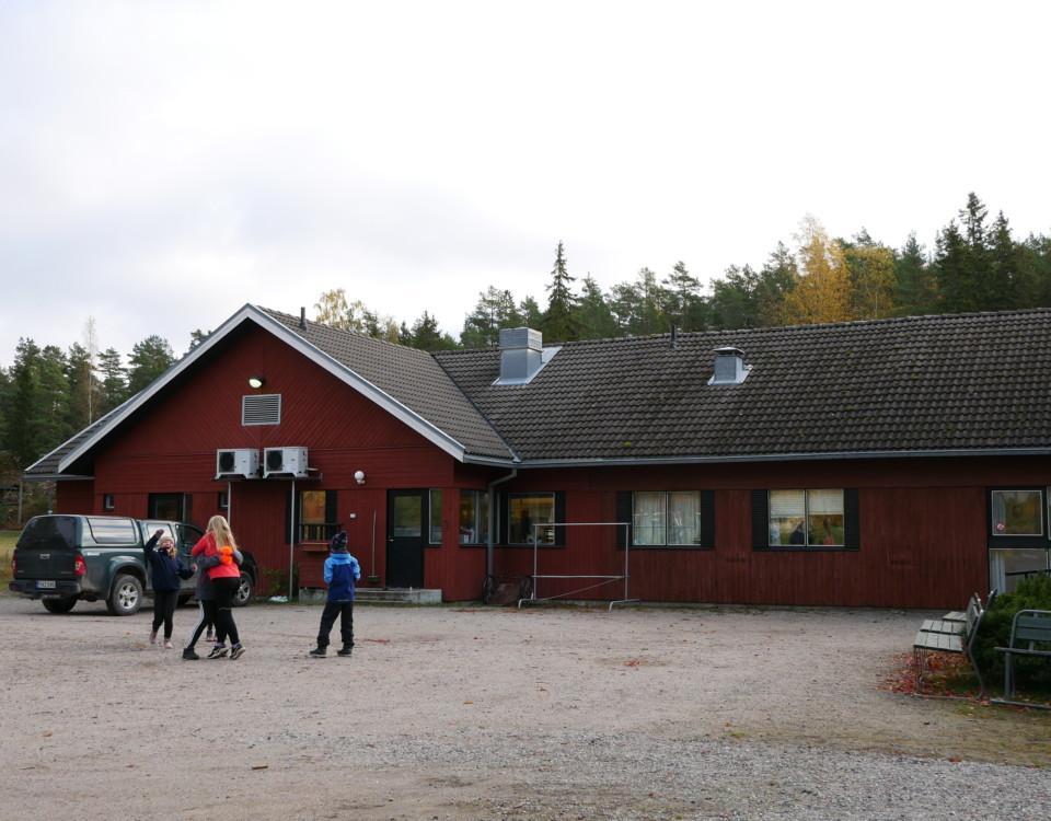 barn vid ett rött skolhus
