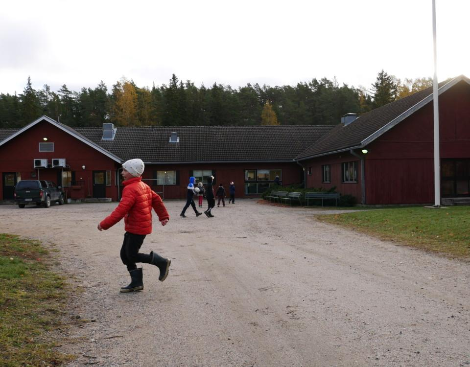 pojke framför ett rött skolhus