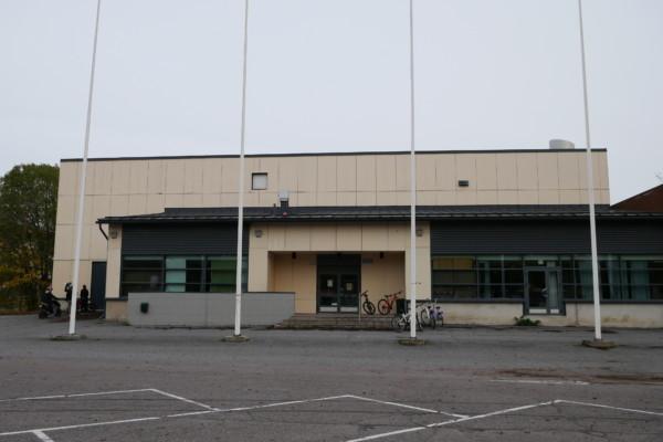 en fyrkantig beige-aktig byggnad bakom fyra flaggstänger