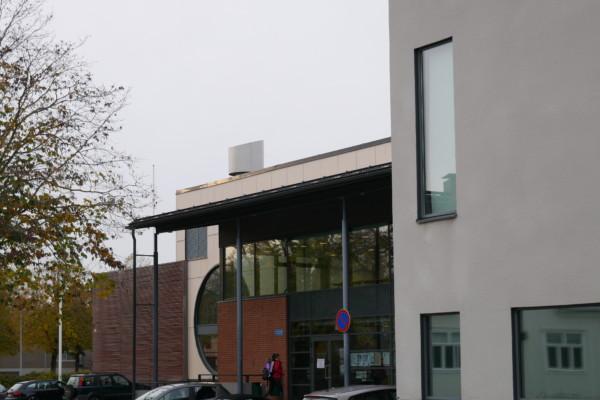 en fyrkantig byggnad och ett höstigt träd