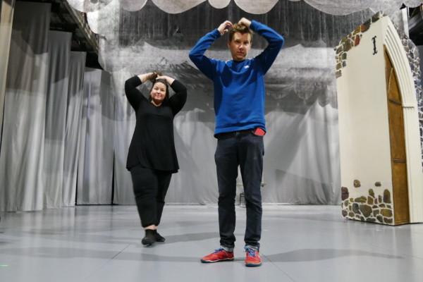 en man och en kvinna står på en teaterscen och fixar till sina hår för kameran