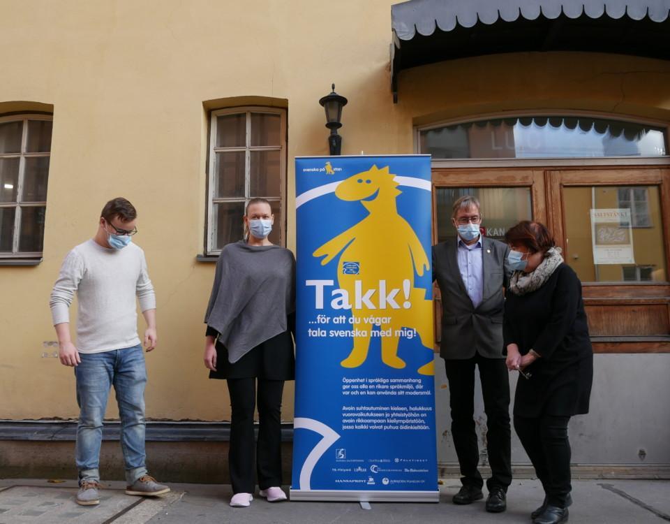 """fyra personer med munskydd står samlade kring en stor banderoll på en gul filur och ordet """"Takk"""" med två k"""