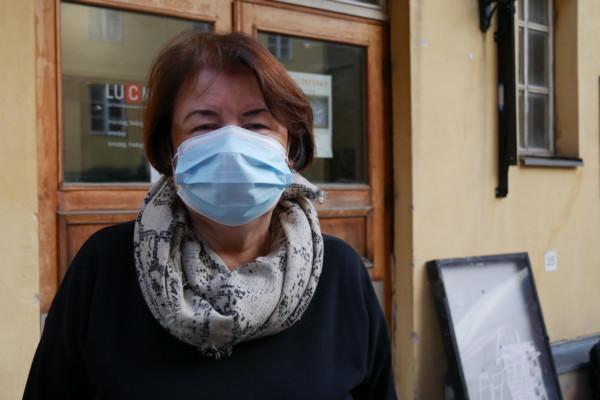 en kvinna med munskydd tittar in i kameran