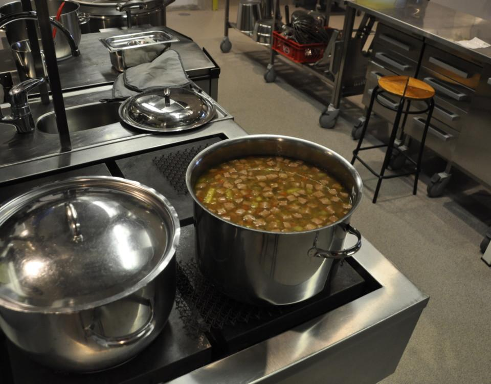 En spis i ett skolkök med kastruller med soppa.