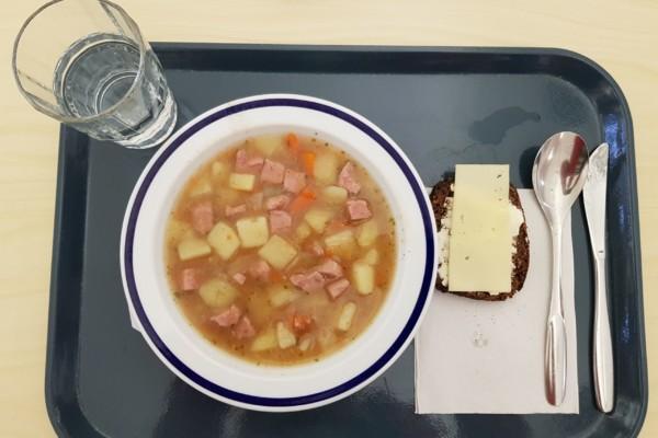 En bricka med en portion korvsoppa, ett glas vatten, ett bröd och bestick
