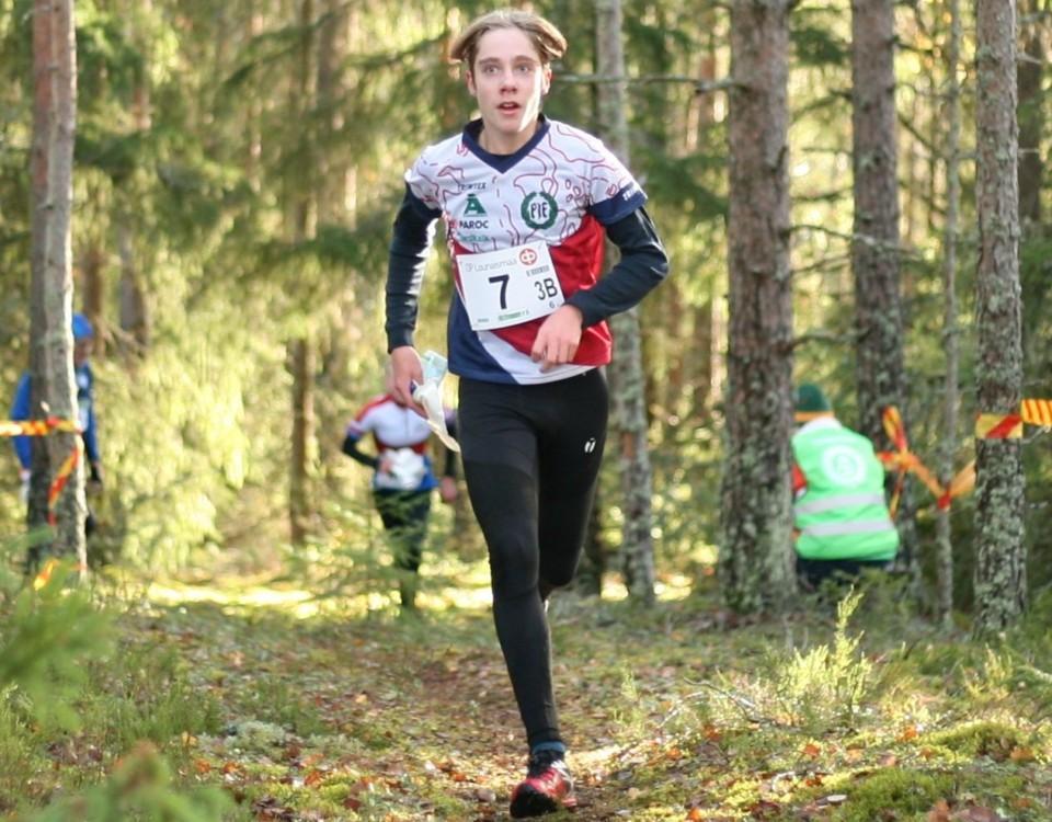 Ung man springer i en skog.