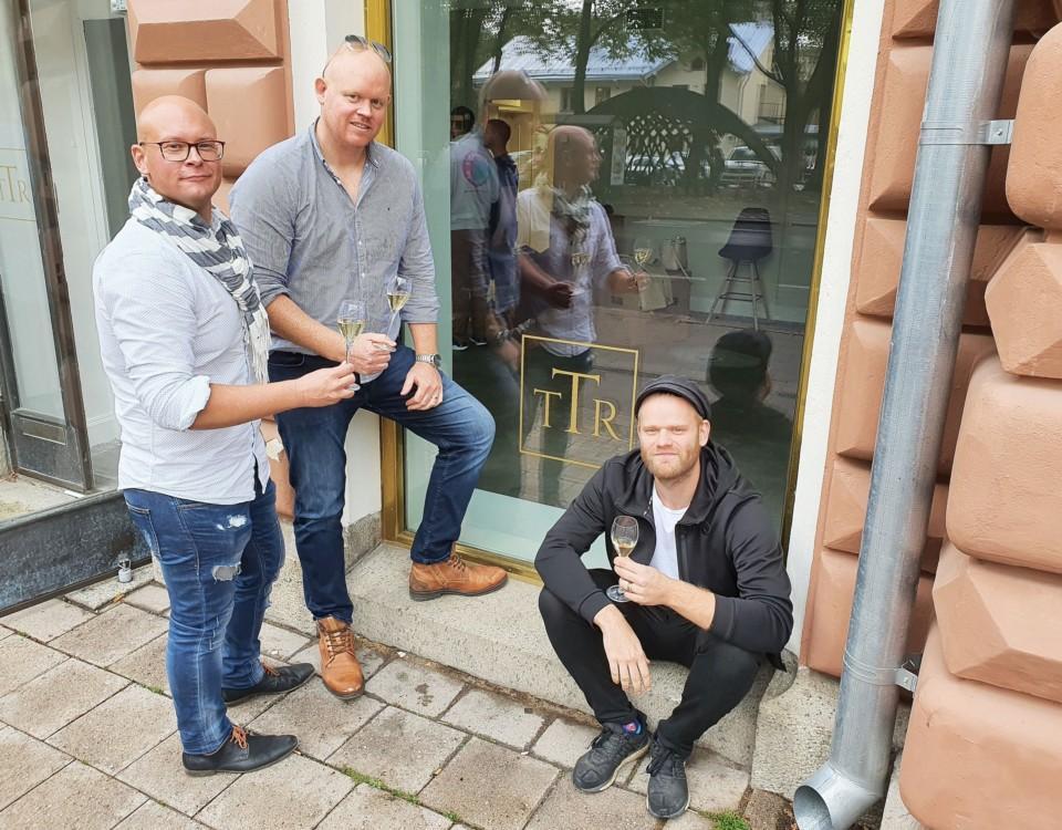 Nordelloch Visser står framför den nya vinbarens fönster, medan Sumelius sitter på fönsterkarmen. Mellan dem syns vinbarens logo, de stiliserade bokstäverna TTR.