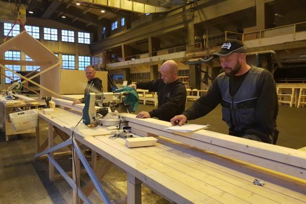 Trä män står vid ett arbetsbord och sågar. I bakgrunden syns ett modulhus.