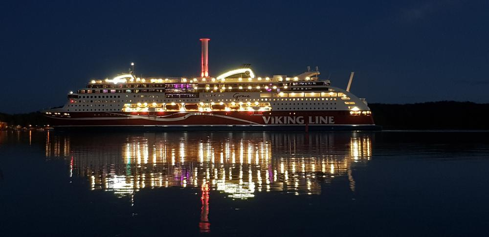 Viking Grace i halvdunkel, med fartygets ljus speglandes i vattenytan.
