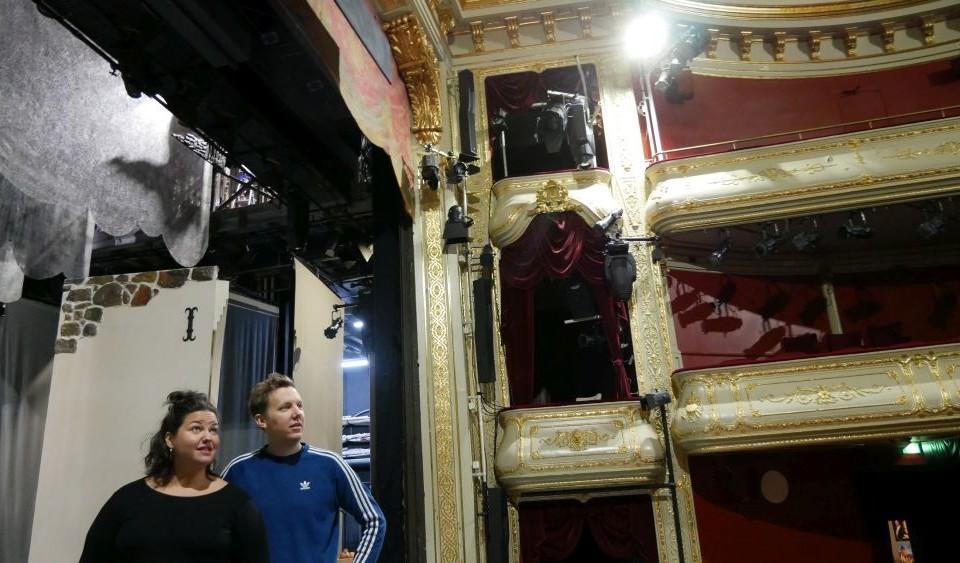 en man och en kvinna står på en teaterscen och blickar ut över en tom salong