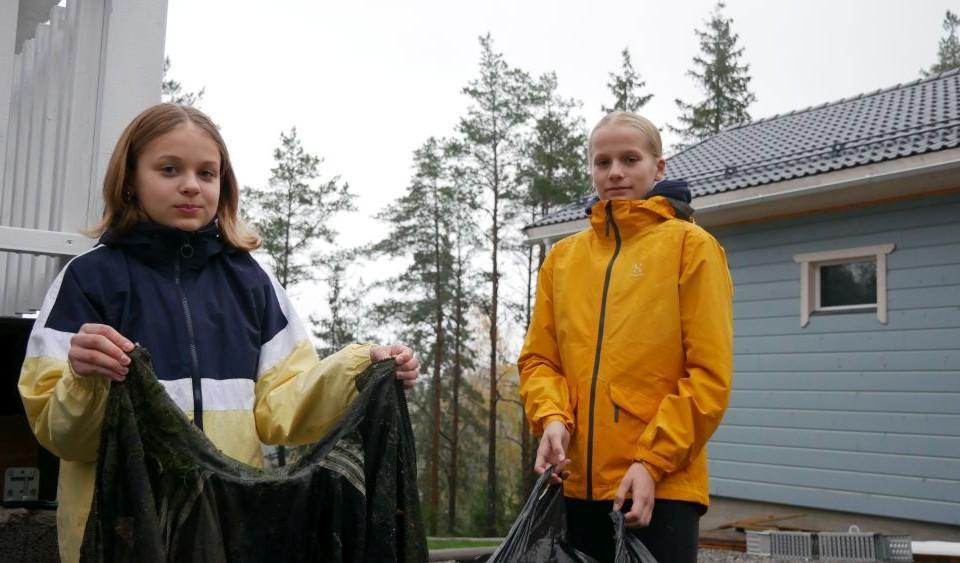 två flickor poserar med skräp de samlat: en mossig jacka och en stor sopsäck