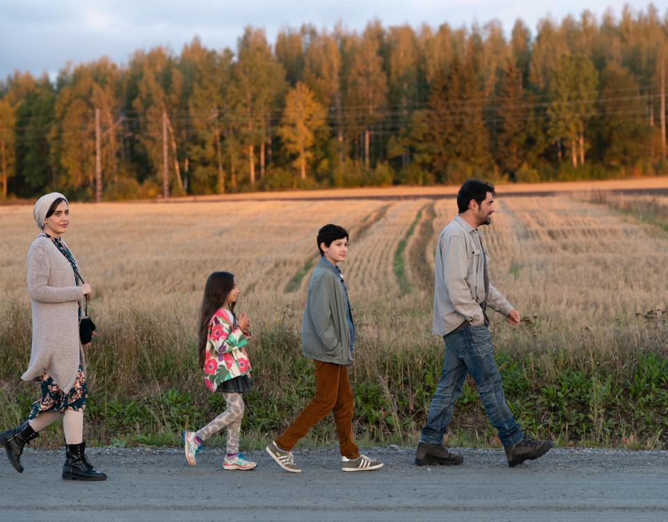 familj spatserar på rad på landsväg