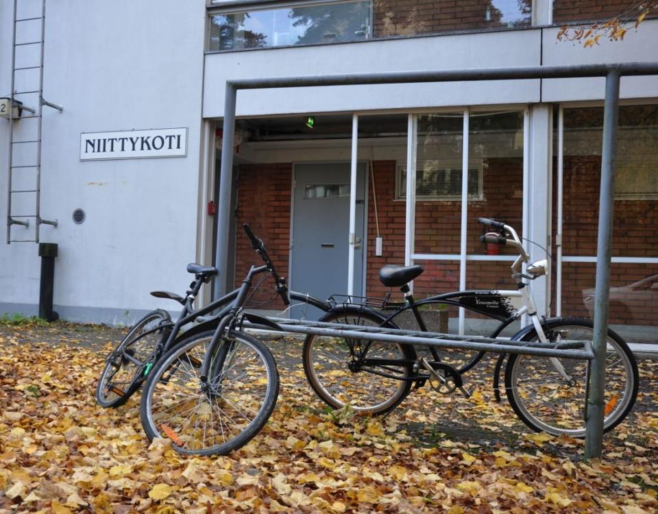 Höstlöv på marken, parkerade cyklar, bostadshus