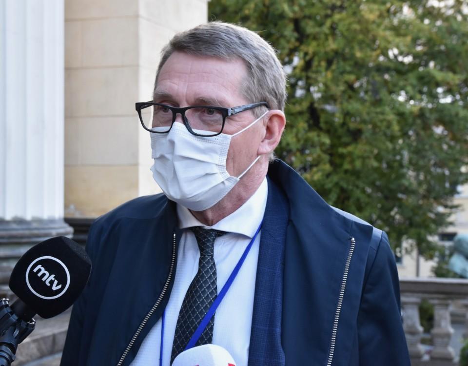 en minister som intervjuas med munskydd på