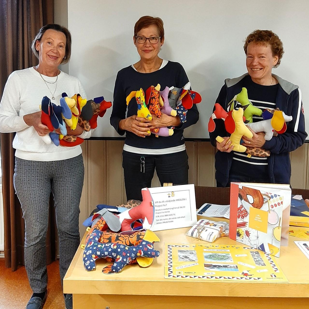 tre kvinnor står med mjukishundar i famnen framför ett bord med en massa kit för föräldrar på sjukhus