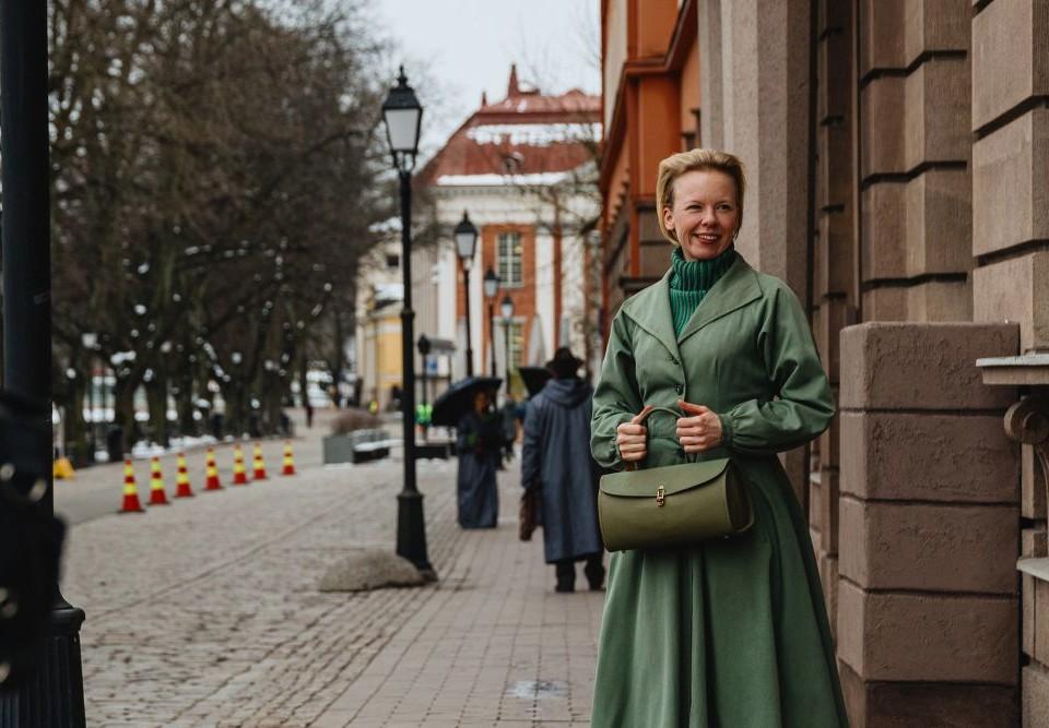 dam i grön kappa står på Åbos gata