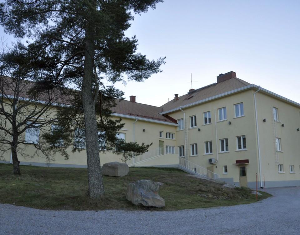 en gul skolbyggnad i sten